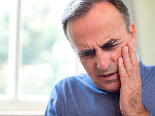 Man in blue shirt who needs an emergency dentist