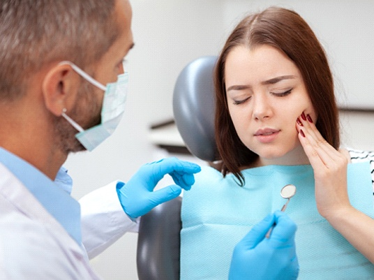 Young woman visiting dentist for emergency dental exam