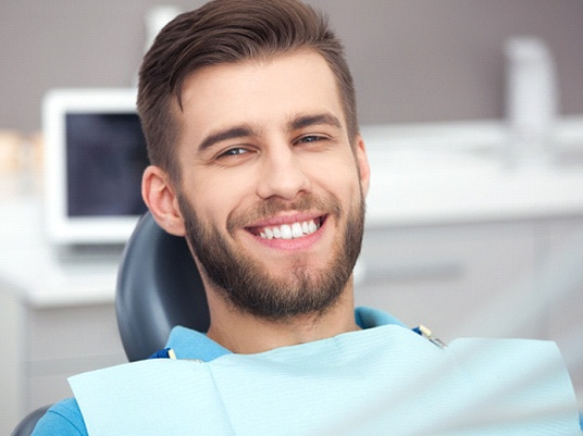 Happy male dental patient after receiving emergency treatment