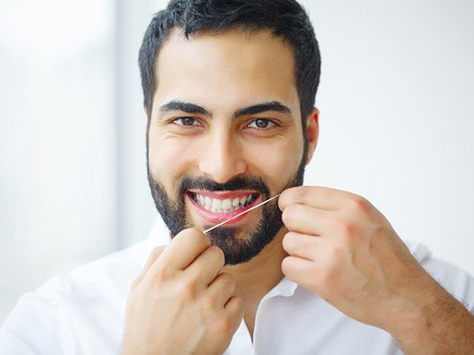 Man in white shirt and brown hair flossing his teeth