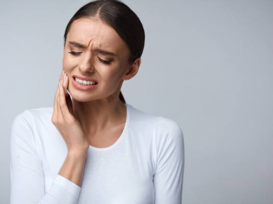 Woman in white shirt with tooth pain