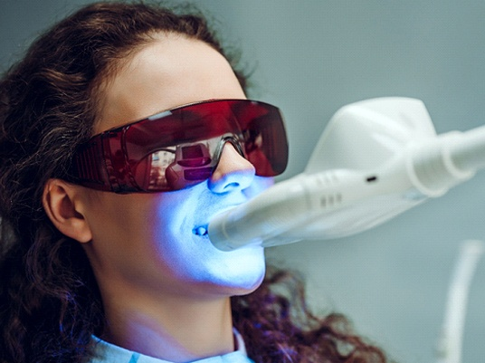 Woman during in-office teeth whitening treatment.